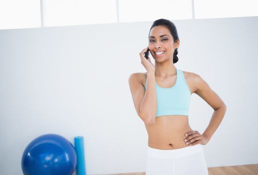 Cheerful slender woman phoning with smartphone