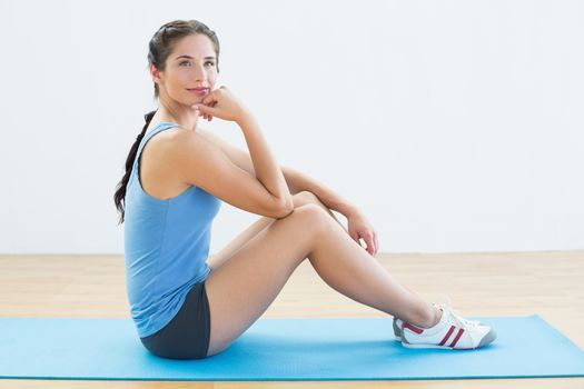 Fit woman sitting upright on exercise mat