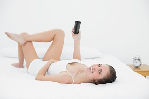 Portrait of a smiling woman with mobile phone in bed
