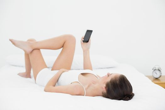 Woman looking at mobile phone in bed