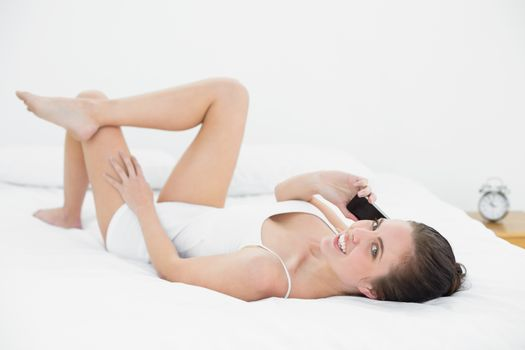 Portrait of a woman using mobile phone in bed