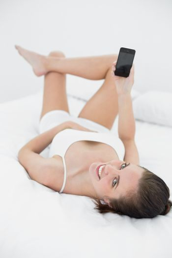 Smiling woman in nightwear with mobile phone in bed