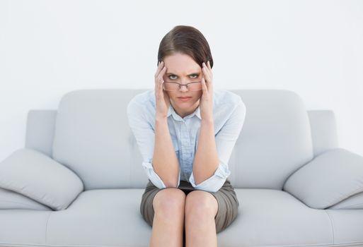 Displeased well dressed woman sitting on sofa