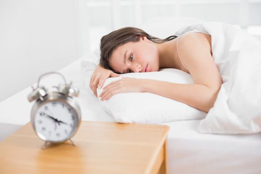 Woman in bed with alarm clock on bedside table