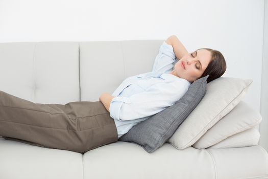 Well dressed young woman sleeping on sofa