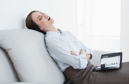 Well dressed woman sitting and sleeping on sofa