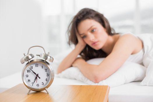 Sleepy woman looking at alarm clock on bedside table