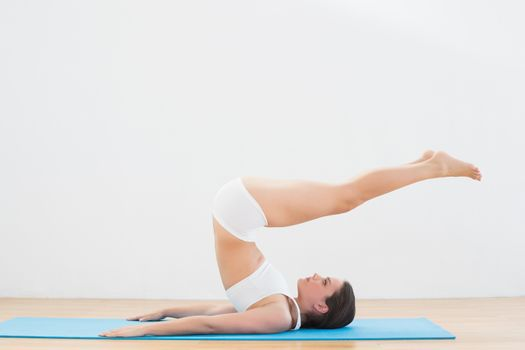 Sporty young woman doing the plough posture