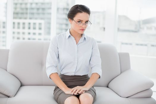Serious well dressed woman sitting on sofa