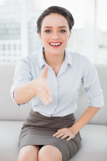 Smiling well dressed woman offering a handshake