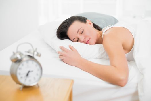 Woman sleeping in bed with alarm clock on bedside table