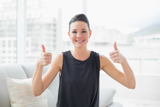 Smiling well dressed woman gesturing thumbs up