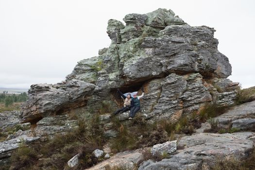Couple on huge rock while on a hike
