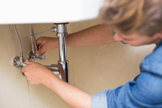 Plumber repairing washbasin drain at bathroom