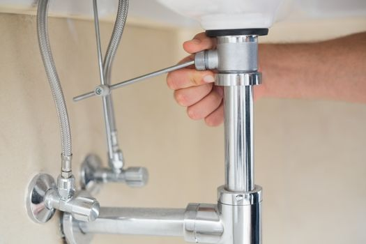 Extreme Close up of a plumbers hand and washbasin drain