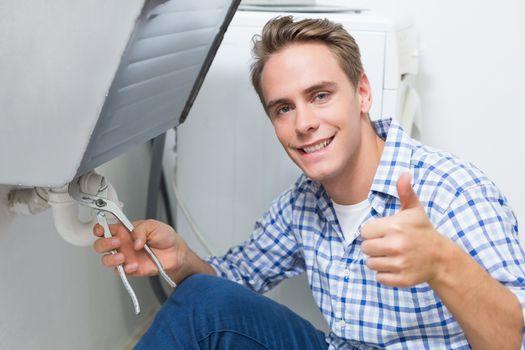 Plumber repairing washbasin drain while gesturing thumbs up