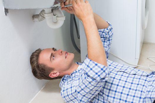 Plumber repairing washbasin drain in bathroom