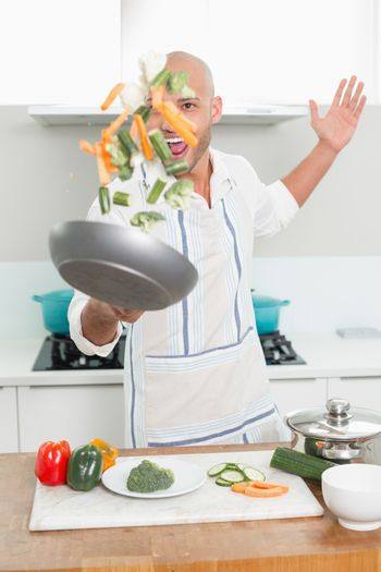 Man tossing vegetables in air at kitchen