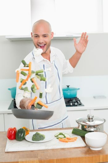 Man tossing vegetables at the kitchen