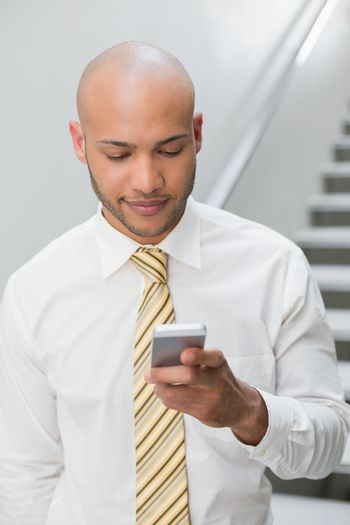 Businessman text messaging against staircase
