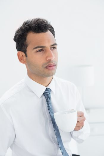 Serious well dressed man drinking coffee