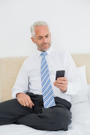 Well dressed man text messaging in bed