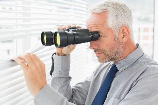 Businessman peeking with binoculars through blinds