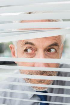 Closeup of a businessman peeking through blinds