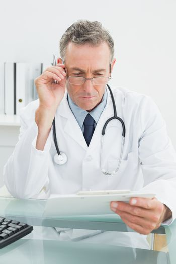 Doctor reading a report at medical office