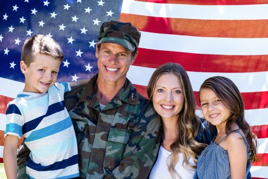 Portrait of american soldier reunited with his family in front of american flag