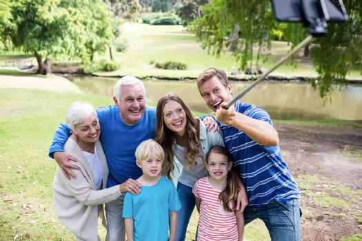 Multi-generation family taking a selfie with selfie stick in the park