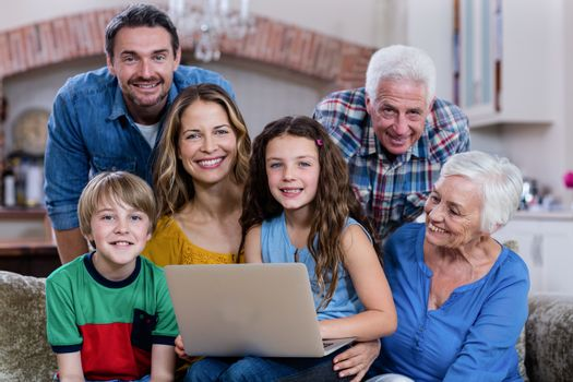 Multi-generation family sitting on sofa and using laptop at home
