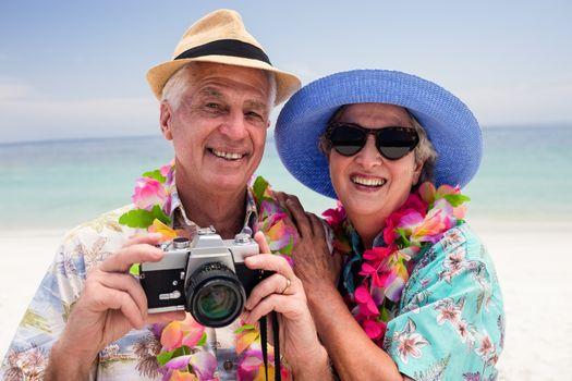 Senior couple clicking a photo with camera