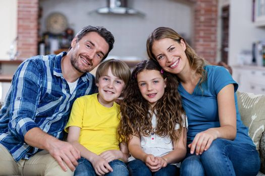 Portrait of happy family sitting on a sofa at home