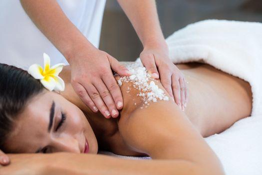 Woman enjoying a salt scrub massage
