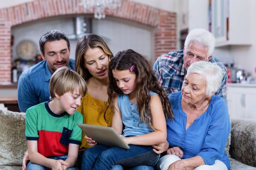 Multi-generation family sitting on sofa and using digital tablet at home