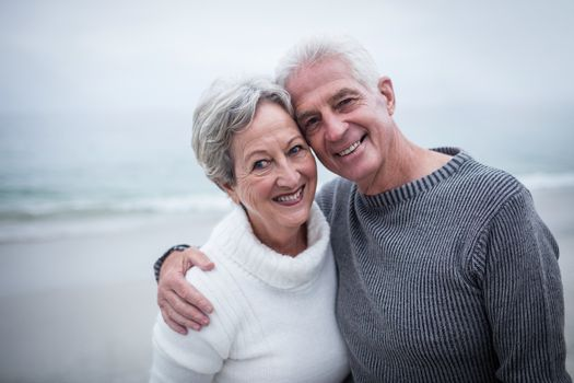 Portrait of happy senior couple embracing on the beach on a sunny day