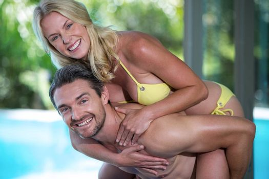 Portrait of man giving a piggy back to woman near the pool