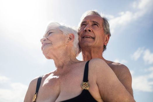 Senior couple embracing on the beach on a sunny day