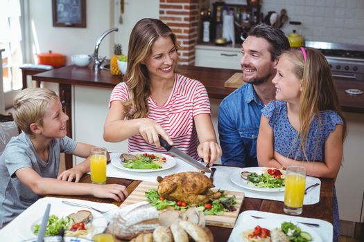 Smiling family celebrating thanksgiving while sitting at dining table