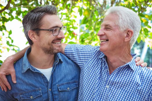 Cheerful father and son with arm around
