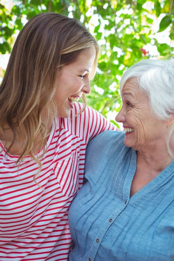 Cheerful mother and daughter with arm around