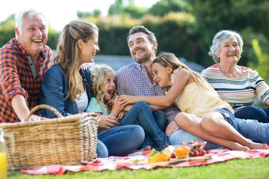 Multi-generation family laughing while sitting on blanket