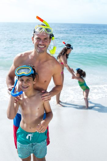 Happy father and son standing against mother with daughter at beach