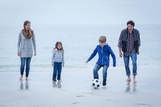 Happy family playing soccer at sea shore