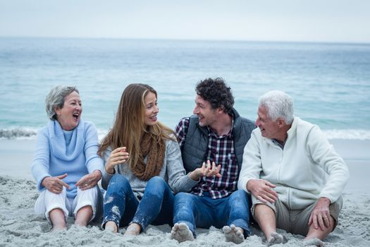Smiling family sitting at sea shore against sky