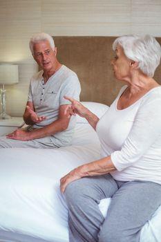Senior couple quarreling while sitting on bed