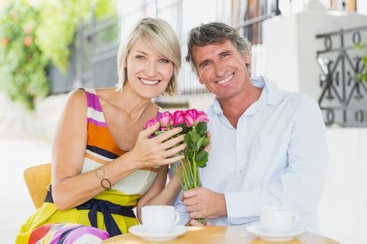Portrait of couple sitting with flower bouquet at cafe
