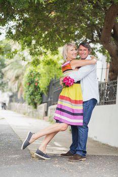 Portrait of couple standing on sidewalk