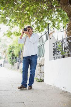 Man photographing on sidewalk